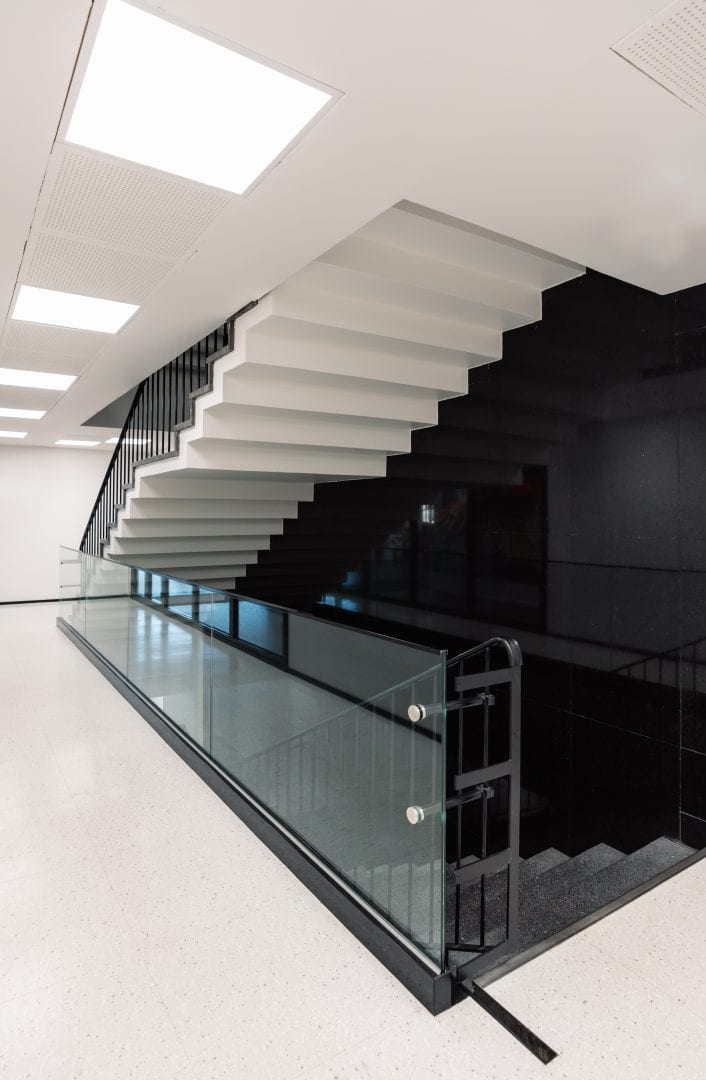 A photo from a moden staircase inside a building. One wall is black, while the floors and space under the stairs going upward are white. The stairs going down are a grey stone colour. There's a glass railing by the stairs.