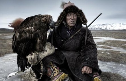 In this Simon Morris photograph titled 'The Mongol', a hunter rests with his hooded eagle outside his home on the plains of Western Mongolia. As well as being a beloved pet, the bird is the key tool the man uses to hunt his prey