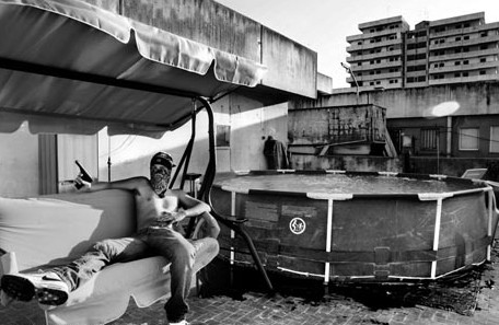 A drug dealer sits with a gun in the notorious Scampia neighbourhood in Naples, Italy in this photograph titled 'What is Missing 01' by Esposito Salvatore. The area is the biggest drug selling neighbourhood in Europe and is controlled by the Camorra mafia