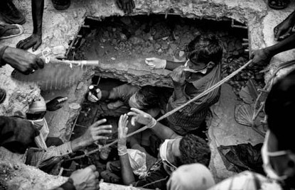 Rescue workers struggle amid the rubble of an eight-storey building which collapsed at Savar, Bangladesh in this stunning photograph by K. M. Asad. More than a thousand garment factory workers died during the collapse, which came just a day after the factory owner boasted the building would 'stand a hundred years'