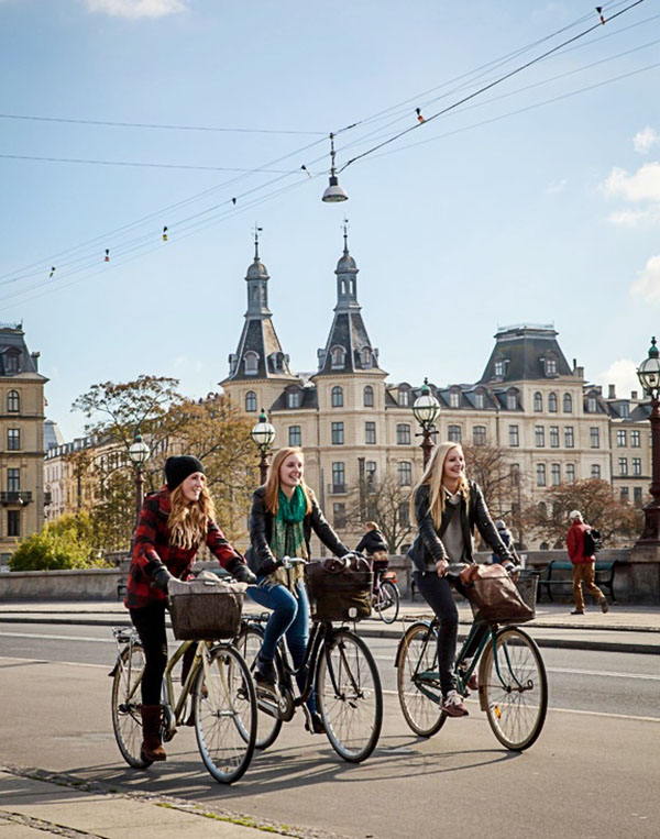 Women riding bicycle by the lakes area in Norrebrogade, Copenhagen, Denmark.