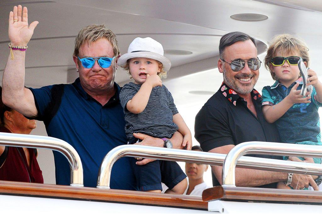 Happy holidays: Elton John holds Elijah, one, and partner David Furnish lifts up three-year-old Zachary