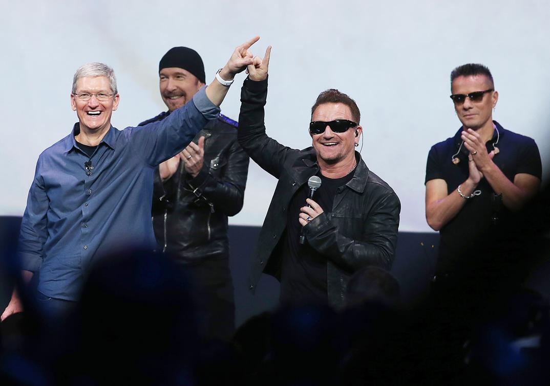 Apple CEO Tim Cook (L) greets the crowd with U2 singer Bono (2nd R) as The Edge (2nd L) and Larry Mullen Jr look on during an Apple special event at the Flint Center for the Performing Arts on September 9, 2014 in Cupertino, California. Apple unveiled the Apple Watch wearable tech and two new iPhones, the iPhone 6 and iPhone 6 Plus. Pic: Justin Sullivan/Getty Images