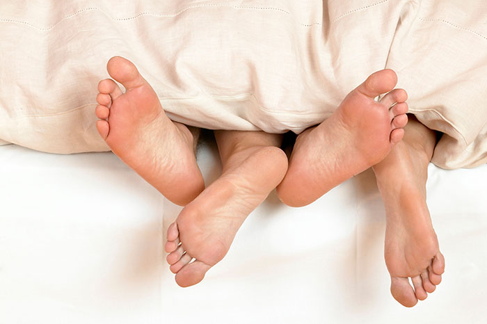 A460BJ Feet of a man and a woman lying on each other in bed