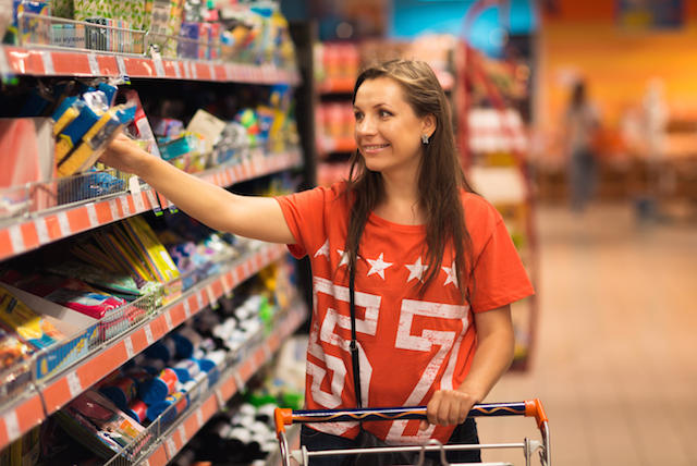 E60J9D Beautiful young woman shopping for cereal, bulk in a grocery supermarket