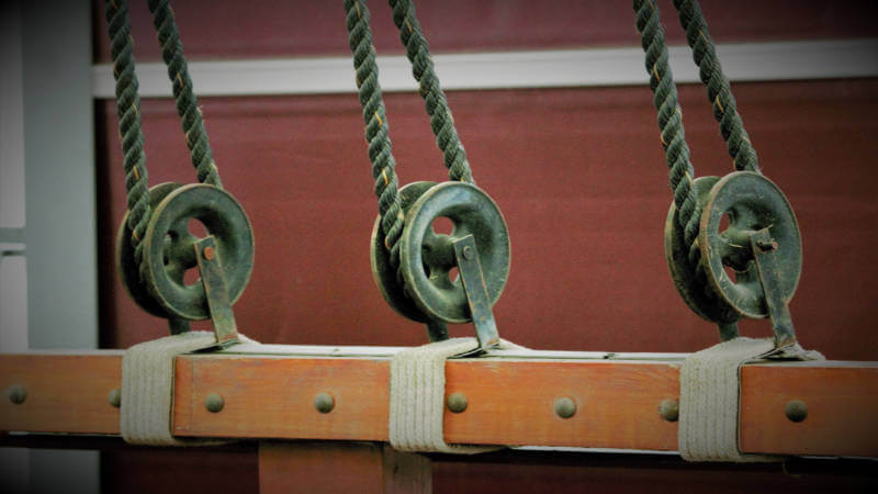 Three pulleys on the side of a ship
