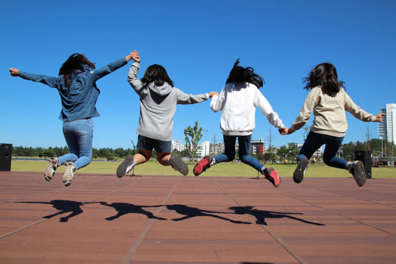 Four children jumping in the air to create shadows on a running track
