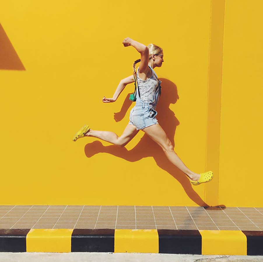 Woman jumping against a yellow wall