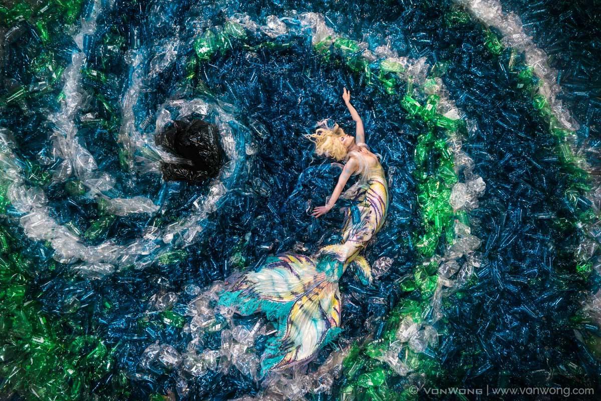 Una sirena posa en un mar de plástico hecho de botellas