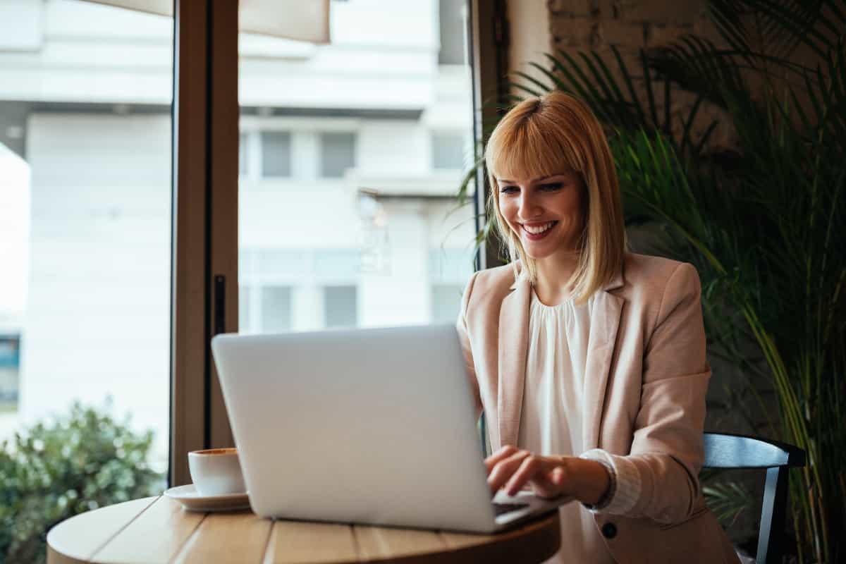 productive business woman smiles using laptop