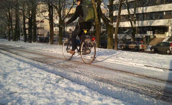 fietsers glibbert over fietspad met sneeuw en ijs