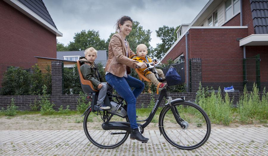 Kirsten, Joas (3) en Seth (1) op de fiets met kinderzitjes