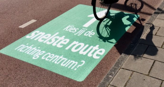 tekst op fietspad: Kies jij de snelste route