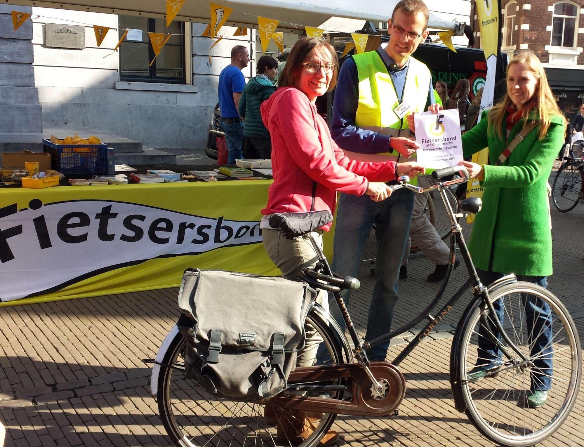 Wethouder Van Hooijdonk (rechts) reikt het eerste nummertje uit aan een fietser zonder licht.