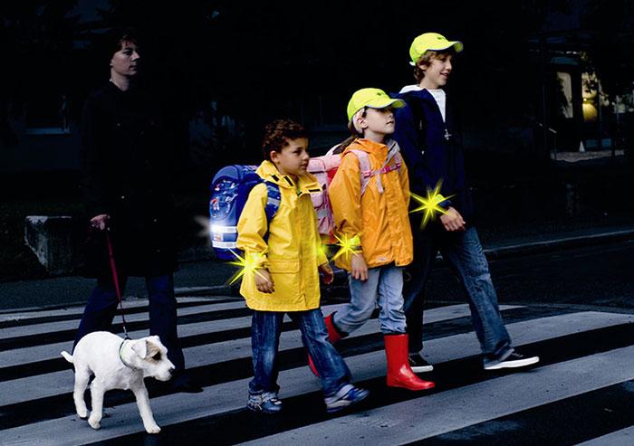 Sichtbare Kinder überqueren nachts Zebrastreifen