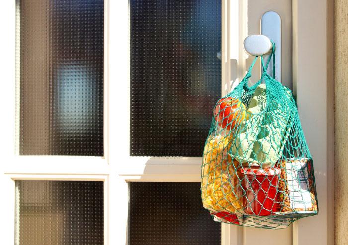 Einkaufsnetz hängt an Türklinke