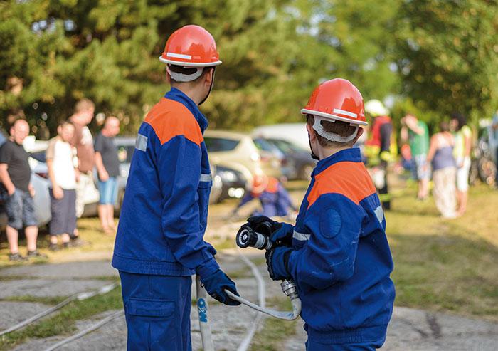 Zwei Mitglieder der Jugendfeuerwehr mit Feuerwehrschlauch