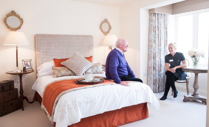 Elderly man on Inspired Villages bed getting care & support