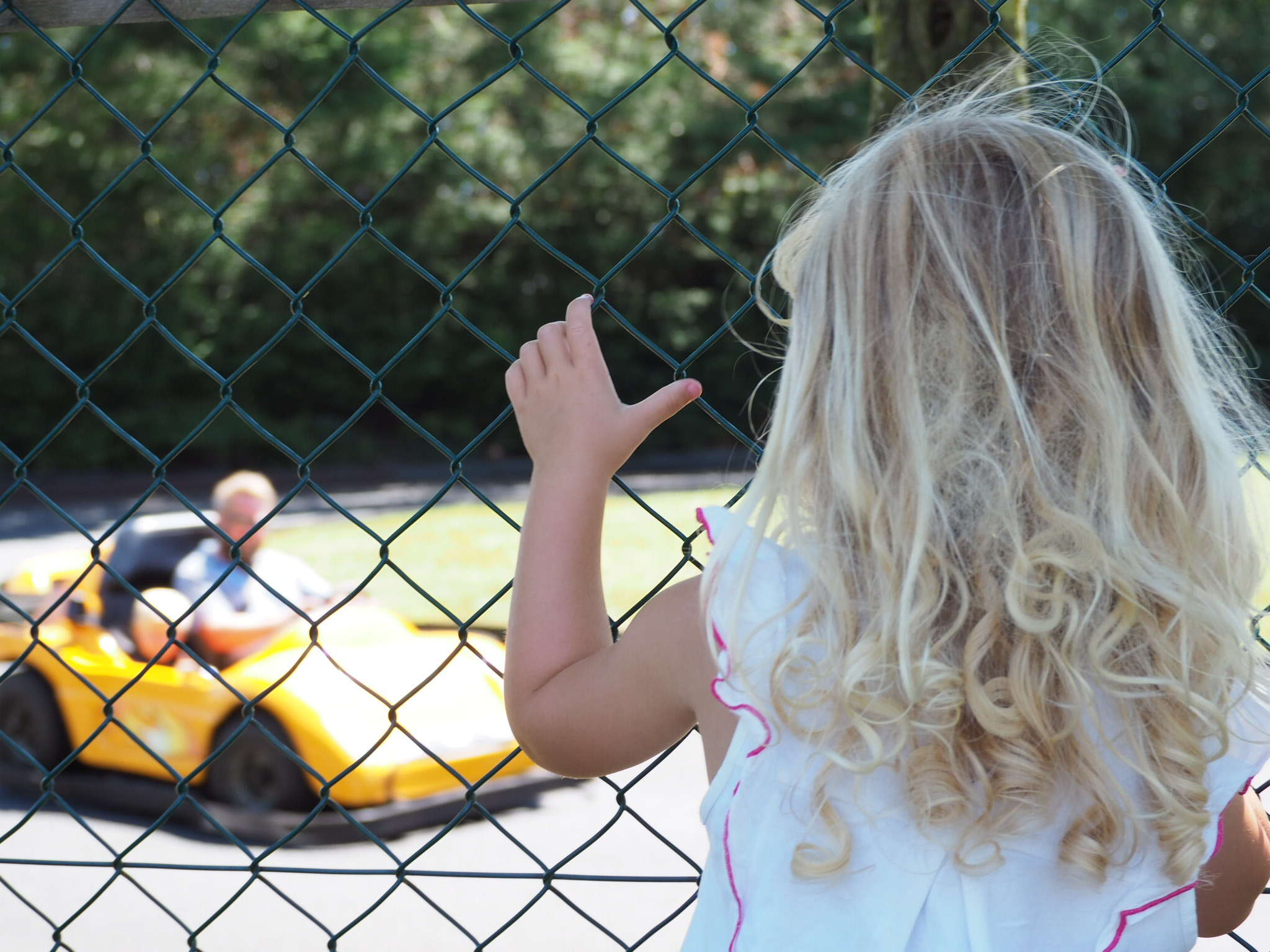 Little girl watching daddy and brother on the go karts at Folly Farm