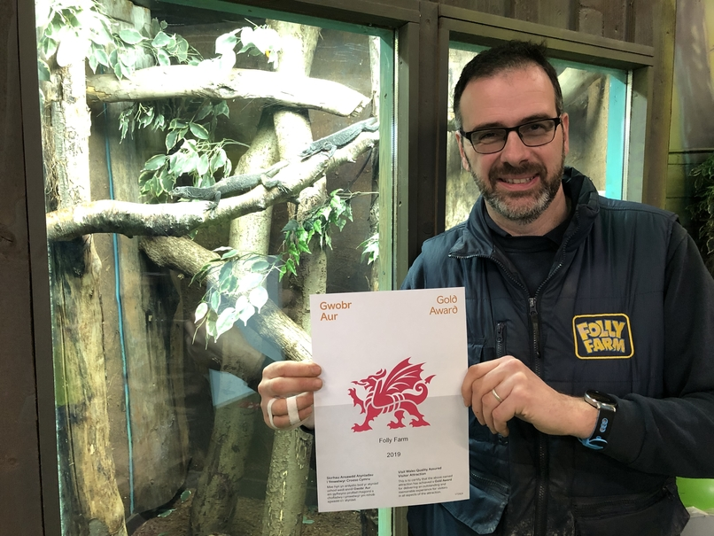 Folly Farm's zoo curator holding the Visit Wales gold award