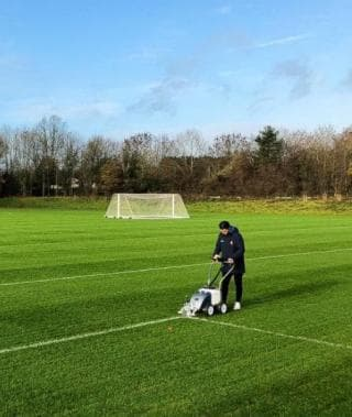 Image of a person maintaining a grass pitch
