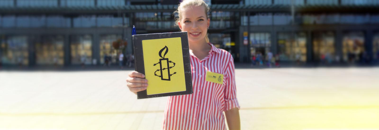 Kuvassa feissari pitää kädessään feissauskansiota, jonka kannessa Amnestyn kynttilälogo.