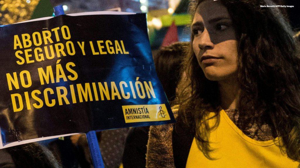 Kuvassa mielenosoittaja espanjankielisen kyltin kanssa, jossa vaaditaan lisääntymis- ja seksuaaliterveysoikeuksia.