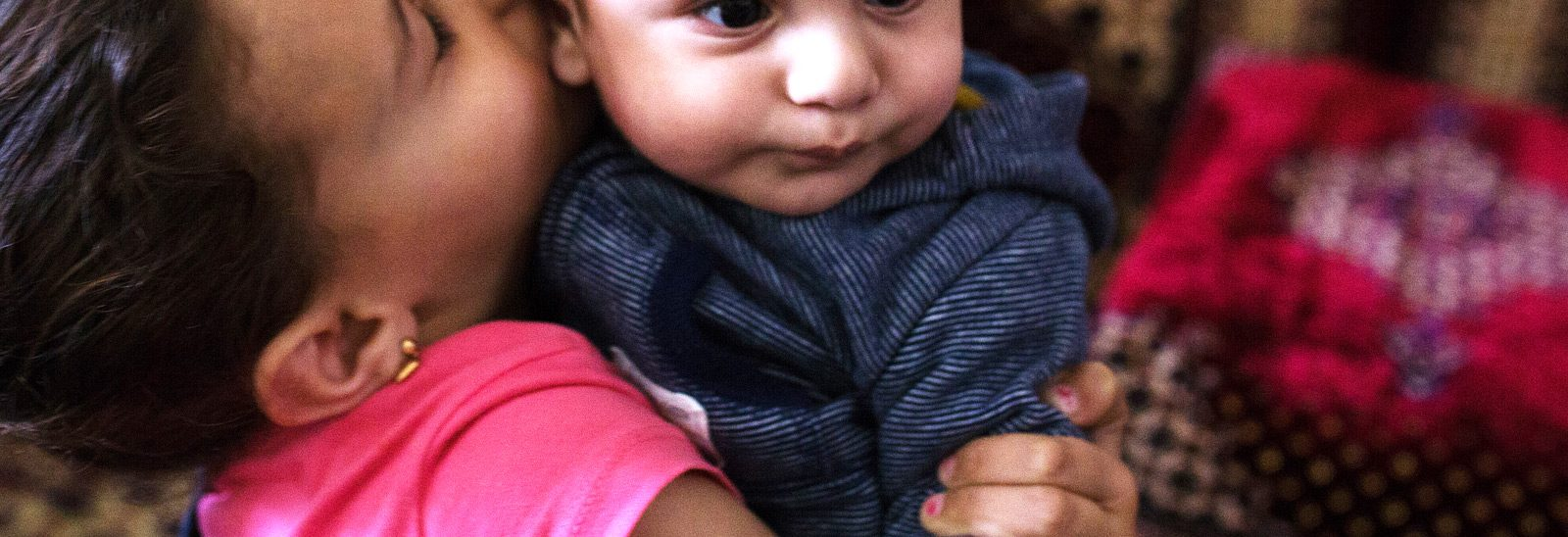 Kuvassa lapsi pussaa hellästi pikkuvauvaa