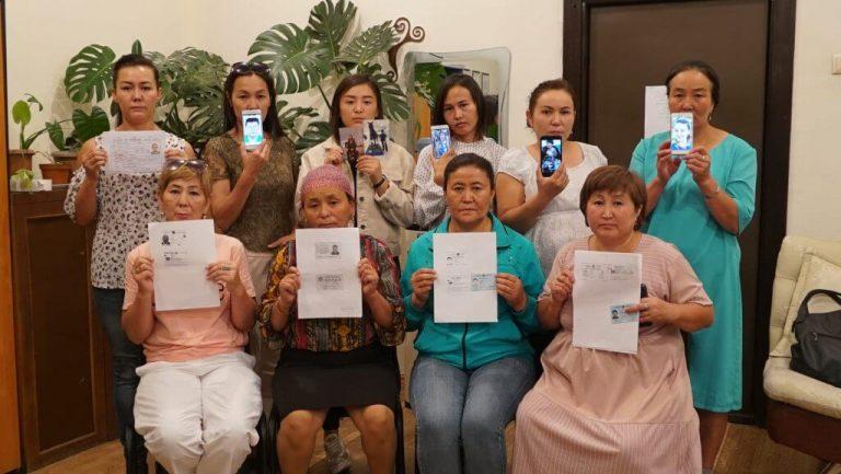 Ryhmä uiguureja esittelemässä kadonneiden omaistensa kuvia