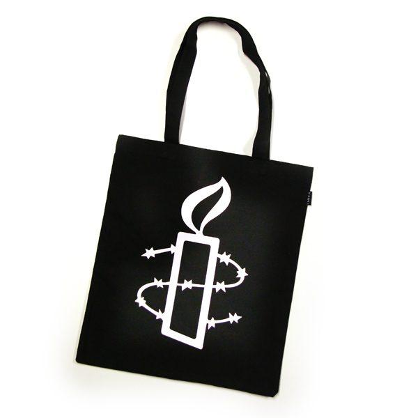 Kuvassa musta kangaskassi, jossa Amnestyn kynttilälogo.