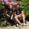 Kuvassa kaksi mallia istumassa kukkivan pensaan edessä Amnesty-paidat päällään.