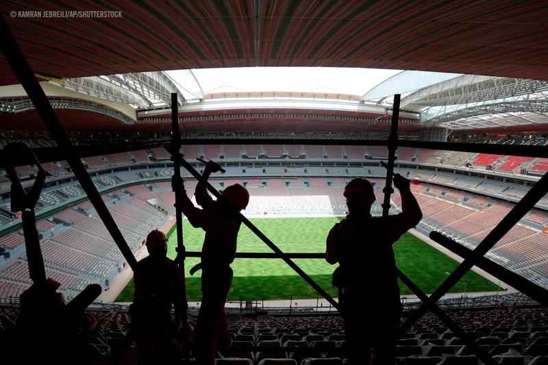 Qatarilaisai siirtotyöläisiä rakentamassa jalkapallostadionia.