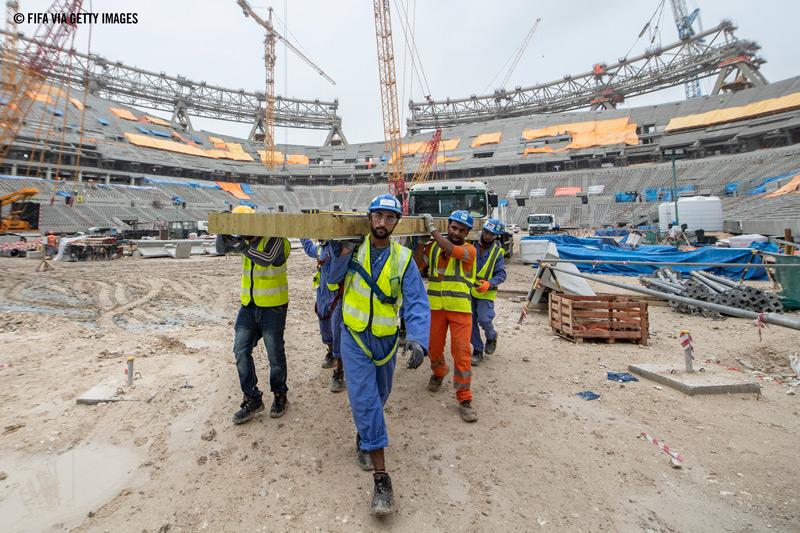Qatarilaiset siirtotyöläiset rakentavat jalkapallostadionia.