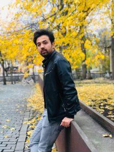 Ali Reza Heidari nojaa aitaan puiston laidalla ja katsoo sivuttain kameraan. Puiden lehdet ovat keltaiset ruskasta.