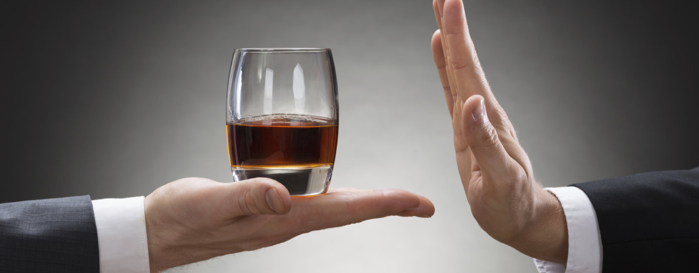 Close-up Of Businessman Hand Reject A Glass Of Whisky Offered By Businessperson