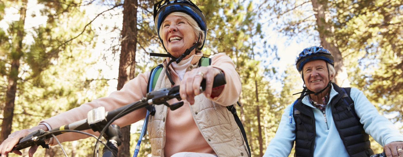 Senior couple mountain biking on a forest trail, low angle