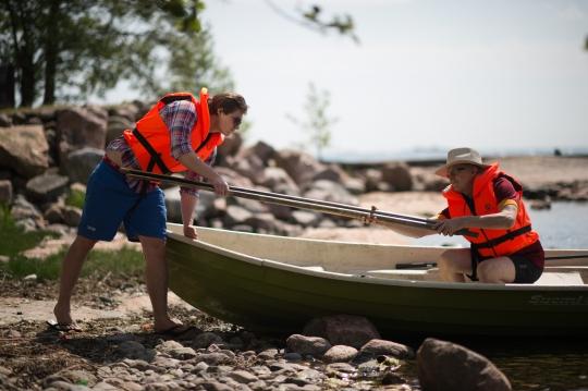 Kaksi miestä laskemassa venettä vesille