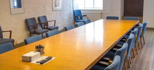 Kokoustila Kurtiini Hamilton-Polhemin pitkä pöytä tuoleineen.