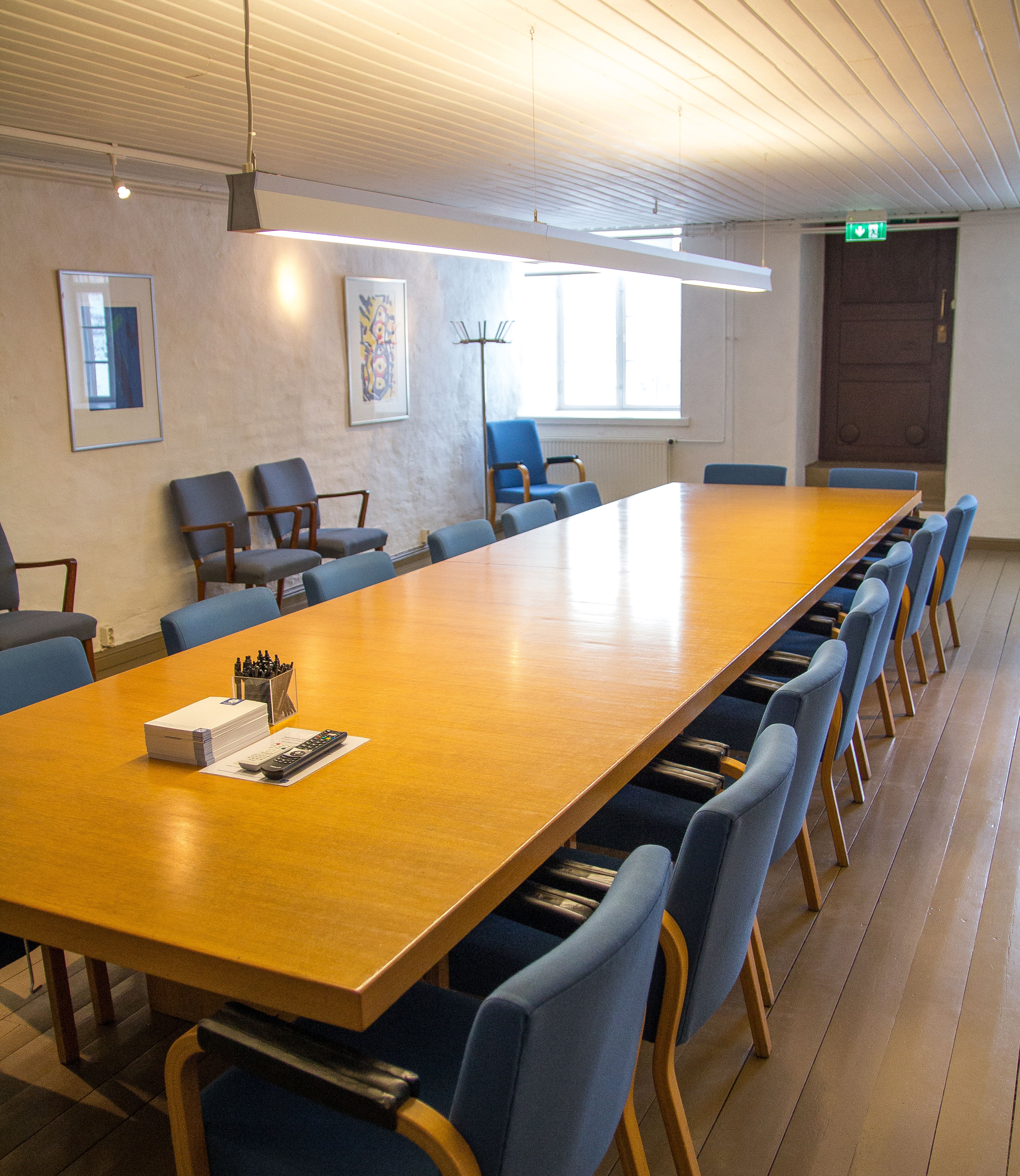 Pitkä puinen pöytä ja sinisiä kokoustuoleja.