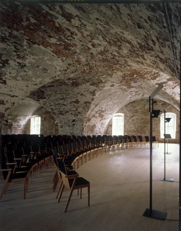 Fersenissä on komea polveileva holvikatto. Tuolit tiiviissä riveissä.