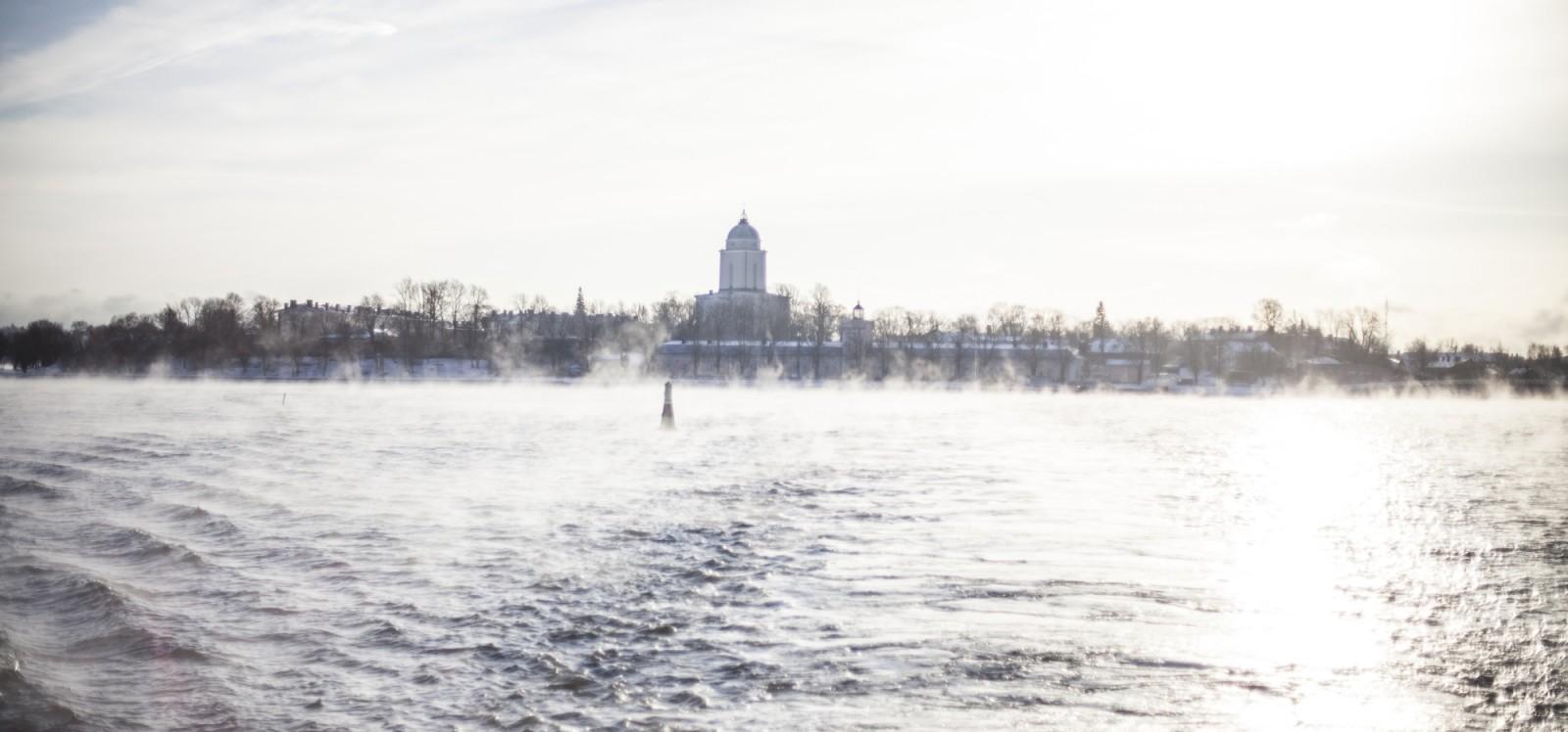 Suomenlinnan kirkko lautalta kuvattuna. Merisumu tuo kuvaan hyisen kylmän tunnelman.