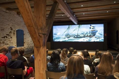 Suomenlinna-museossa takaapäin kuvattu yleisö katsomassa lyhytelokuvaa Suomenlinnan historiasta.
