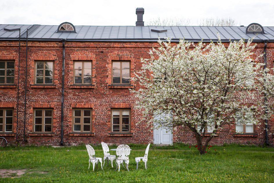 Kuvassa tiilitalo, kukkiva omenapuu ja valkoiset puutahakalusteet.