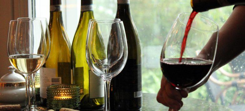 Kolme viinipulloa joiden vieresssä kaadetaan punaviinia lasiin.