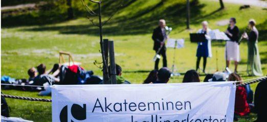 Kuva puhallinorkesterista soittamassa nurmialueelle, edustalla banneri, jossa lukee Akateeminen puhallinorkesteri