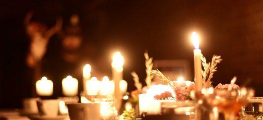 Valokuvassa pöytä on katettu astioin ja valaistu kynttilöin.