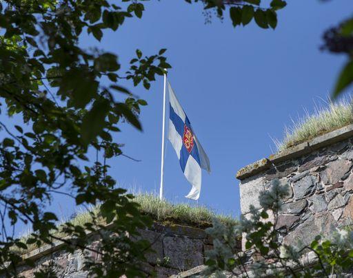 Suomen lippu liehuu muurien välistä kesäisenä päivänä.