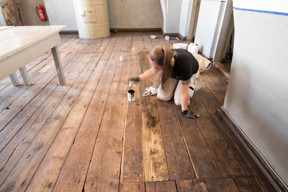 Maalari Mari Kirveslahti uutta lattialankkua patinoituneen näköiseksi.