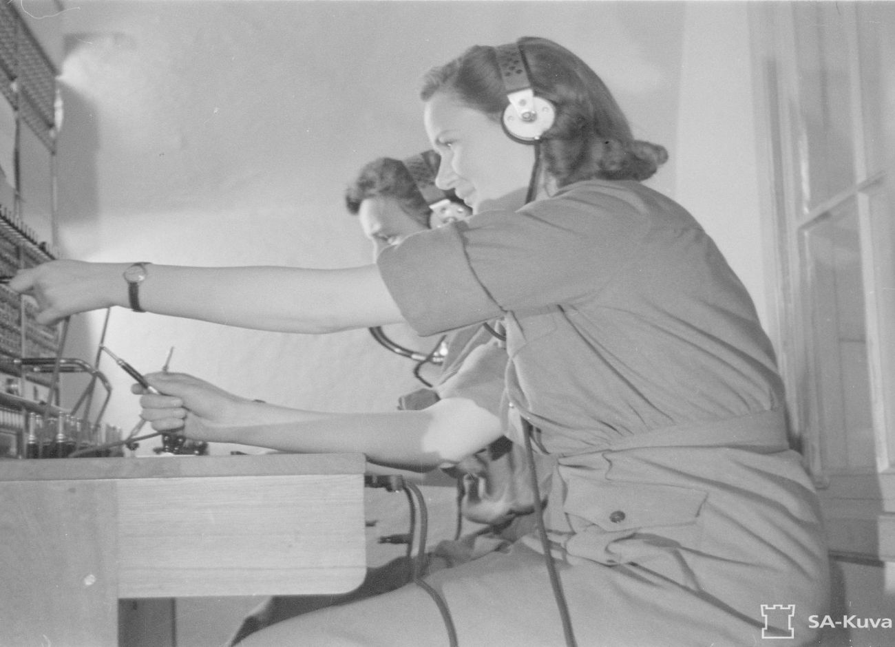 Mustavalkoinen historiakuva, jossa kaksi naista on kuvattuna sivusta työskentelmässä ilmavalvontavuorossa kuulokkeet korvilla