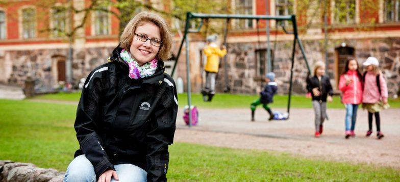 Kuvassa Terhi Riihimäki istumassa keinupuiston laidalla. Taustalla leikkiviä lapsia syysmaisemassa.